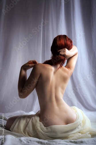Back view of a naked woman sitting in bed - 68279303