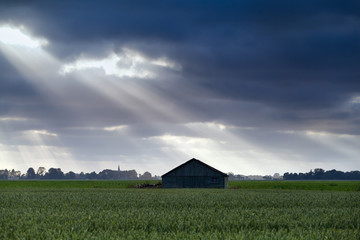 wooden hut over sky with sunbeams