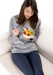 Beautiful woman relaxing on the sofa and eating a fruit salad