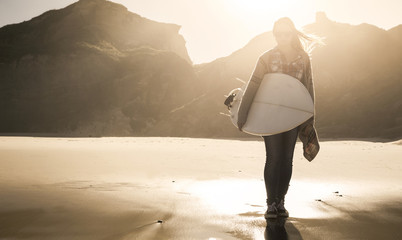 Portrati of a surfer girl on the beach agaist the sunlight