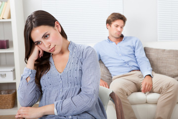 Upset Woman With Man Sitting On Sofa In Background