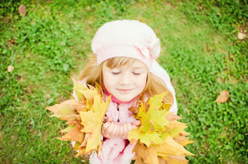 Autumn portrait of little pretty happy child (girl) with maple l