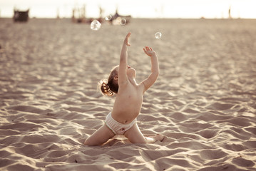 Baby girl playing with soap bubbles on the beach