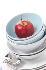 empty bowls, plates and red apple, close-up, isolated