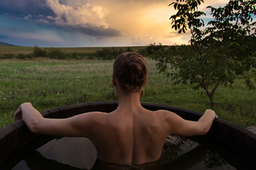 Bathing woman relaxing in outdoor bath or tub