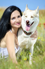 Beautiful woman with husky outdoors.Happy brunette woman with sm