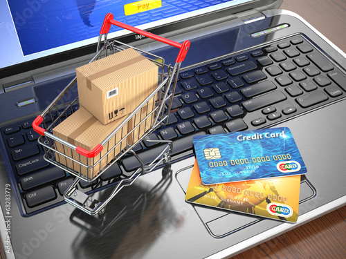 E-commerce. Shopping cart and credit cards on laptop.