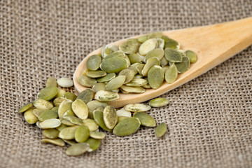 Pumpkin seeds in a wooden spoon.