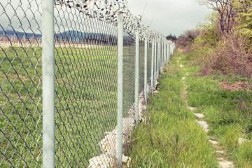 Fence with barbed wire at the state border.