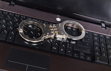Metal handcuffs on black laptop keyboard
