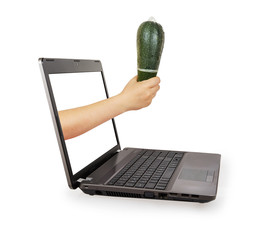 Woman's hand holding green zucchini with a condom from a laptop