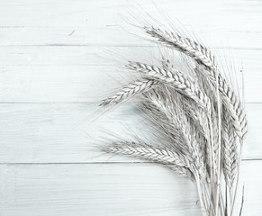Ears of wheat isolated on wooden background