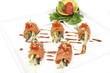 Fish rolls with herbs and fruit on a plate