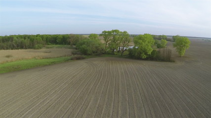 Over the opened rural  field and lake. Aerial