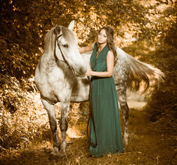 woman with white horse at forest path