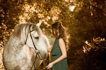 woman in green with horse in forest