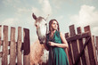young woman and white horse at farm fence