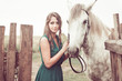 woman in green dress and white horse