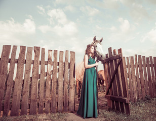 woman and horse at open wooden farm gate