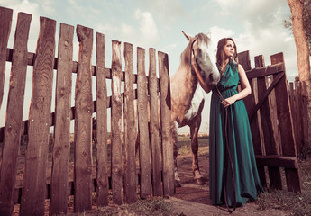 woman in green holding horse at open wooden fence