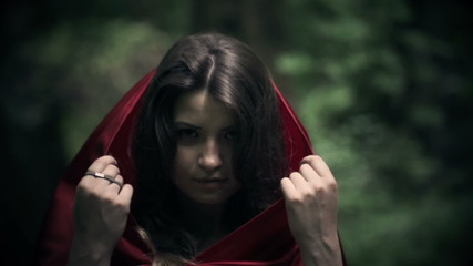 Mysterious beautiful woman, red riding hood in the forest