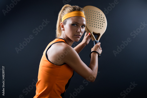 Poster Beautiful woman playing padel indoor. Isolated on black.