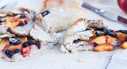 pieces of biscuits with peach and blueberry on a white table
