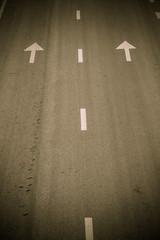 arrow symbol and white stripes on asphalt road