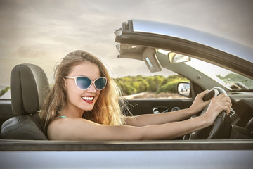 beautiful blonde woman who is driving an elegant car