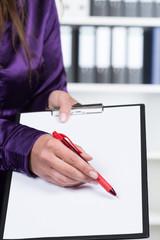 Frau zeigt mit einem Stift auf ein Klemmbrett