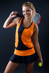 Sporty teen girl tennis player with racket. Isolated on black.