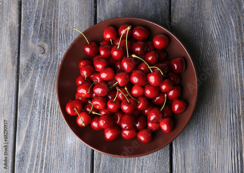 Sweet cherries  on plate on wooden background