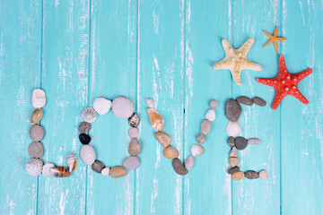 Word love made from sea shells and stones on wooden background