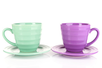Bright cups and saucers isolated on white