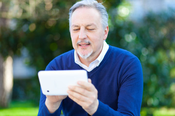Senior man using a digital tablet outdoor in the park