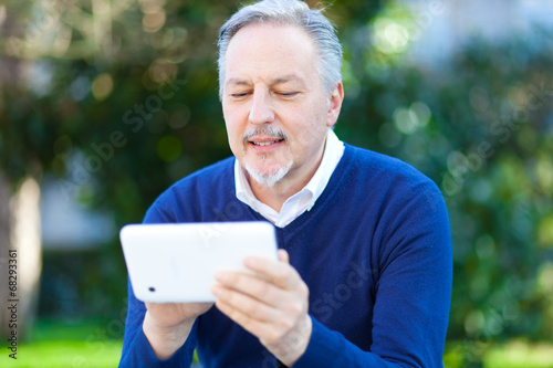 Senior man using a digital tablet outdoor in the park