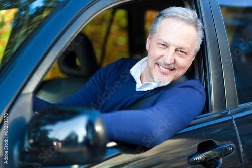 Senior driving his car