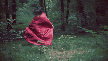 Woman in red cape running away in forest