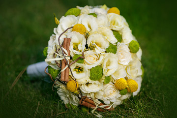 Wedding bouquet from beige roses, cinnamon, a lemon, a lime