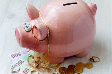 Fat pink saving pig with money and jewelry