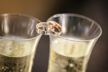 wedding rings lie on champagne glasses