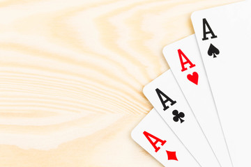 Four aces on wooden background
