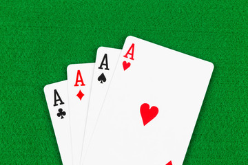 Four aces on green felt background