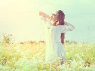 Beautiful teenage model girl in white dress enjoying nature