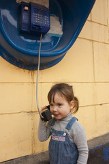 Девочка разговаривает по стационарному уличному таксофону