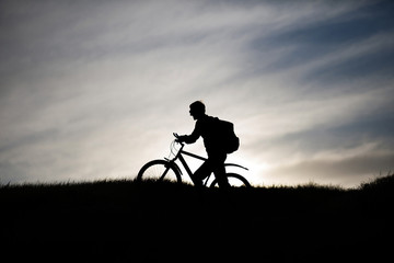 silhouette of a cyclist on a mountain