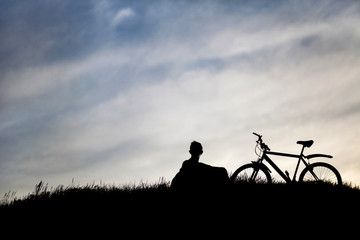 Silhouette of tourist and bike on sky background