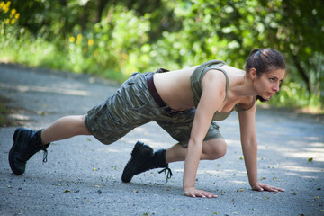 Beautiful military woman training push-ups in park