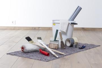 Wohnung streichen mit Farbroller, Pinsel, Eimer auf Malerfilz