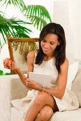 Beautiful young elegant woman sitting in livingroom using